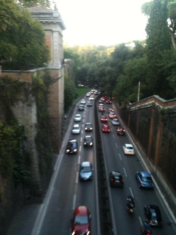 Cars drive under a bridge at Villa Borghese.