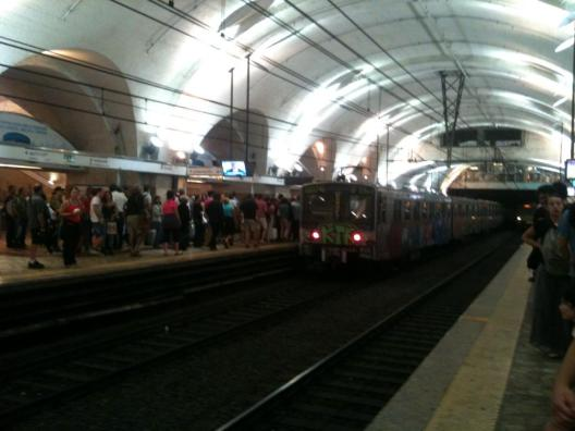 The metro stops still halfway though the tunnel in termini at rush hour.